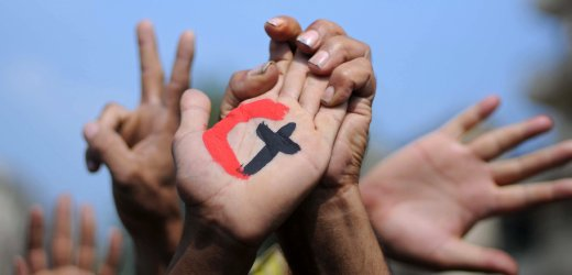 TOPSHOTS A cross and a crescent are painted on the palm of an Egyptian demonstrator holding the hand of a fellow protester during a rally in support of national unity in Cairo's Tahrir Square on October 14, 2011, days after 25 people, mostly Coptic Christians, were killed in weekend clashes with Egyptian security forces. AFP PHOTO/MOHAMMED HOSSAM
